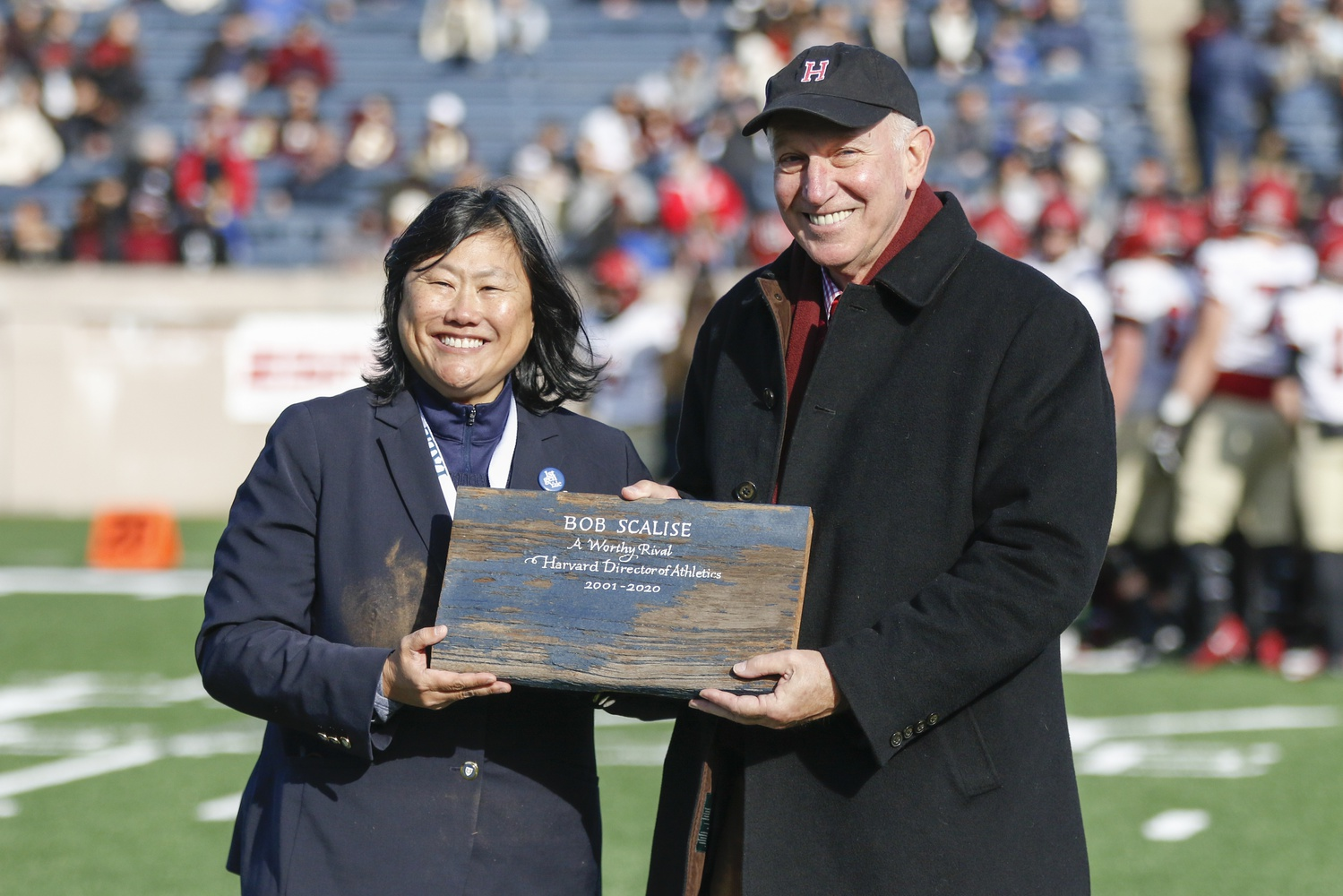At the 136th rendition of The Game,  Yale's Director of Athletics, Victoria M. Chun, honored her Harvard counterpart, Robert L. Scalise, with a piece of the original Yale Bowl.