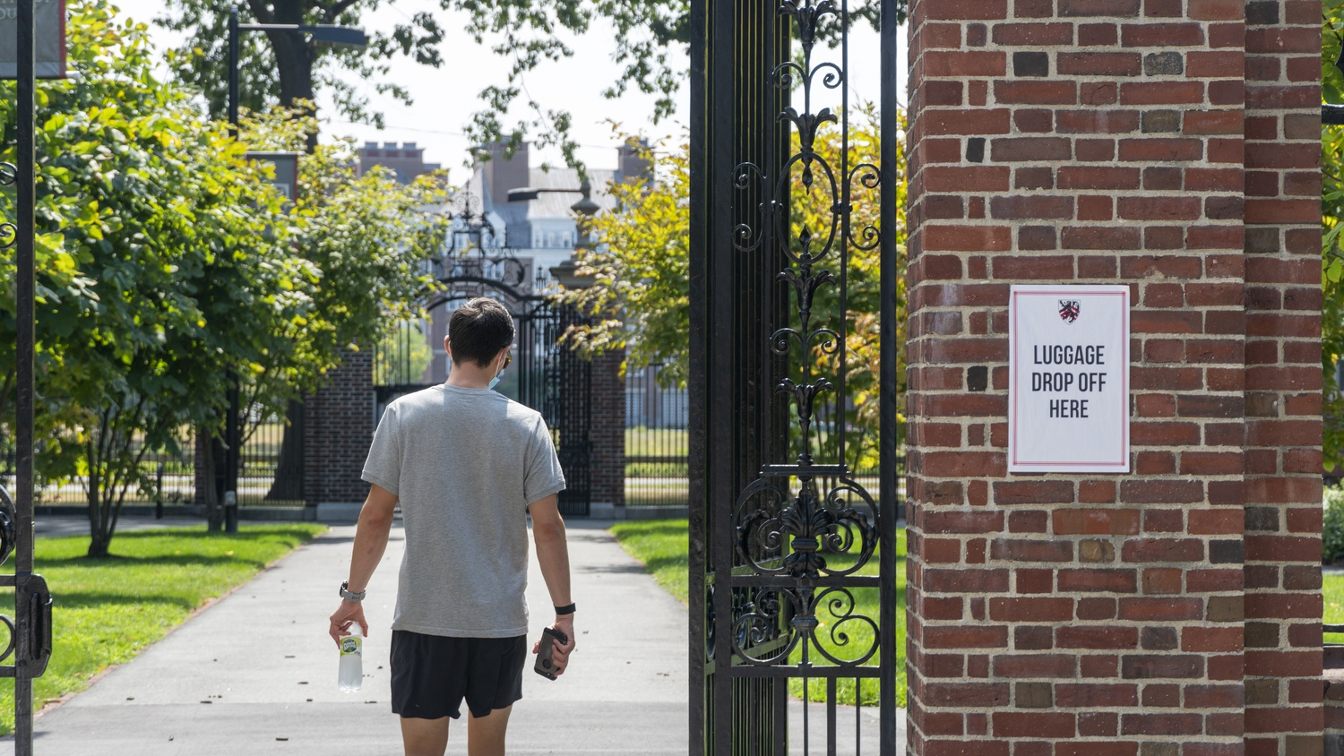 A student walks through the gates of Winthrop House during fall 2020 move-in. This spring, Harvard will expand the number of students living on campus and prioritize upperclassmen.