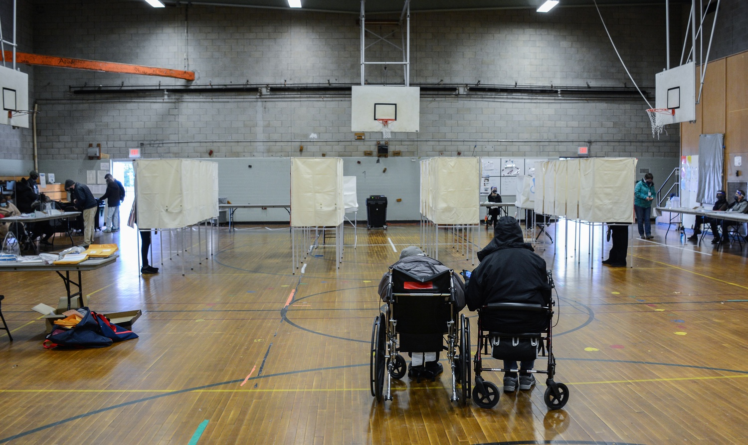 Two voters waiting for transportation back to their homes look on as voters cast their ballots at Graham and Parks School polling center in Cambridge, Mass. on Tuesday.