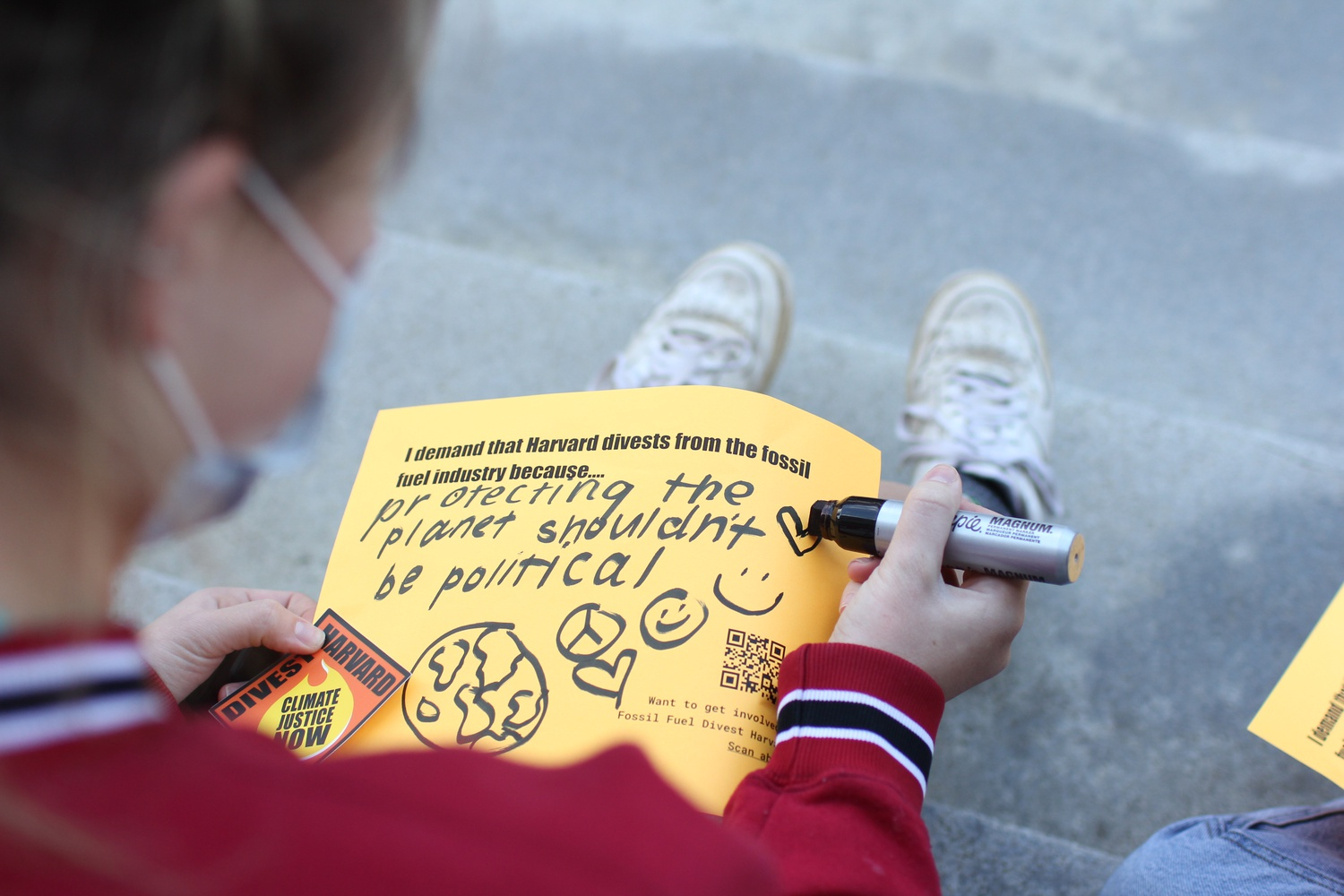 A student makes a sign at a Divest Harvard rally in front of Widener Library in November 2020.