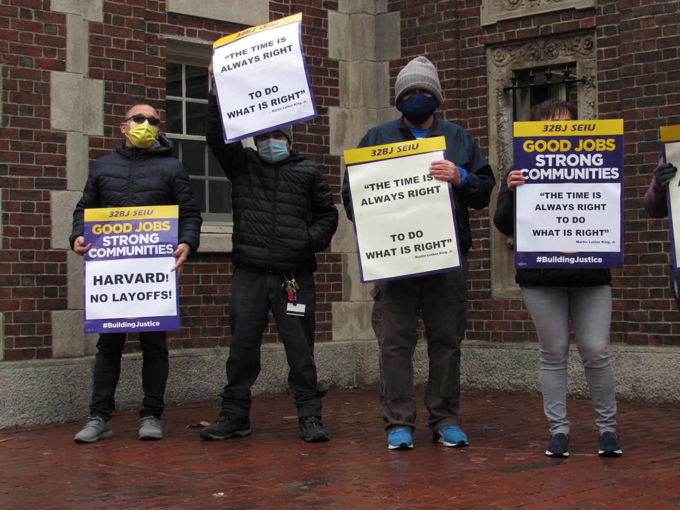 Itamar San Giorgio, left, a contracted custodian who works at Widener Library, protests Harvard's impending layoffs with fellow 32BJ SEIU members next to the Widener Gate.