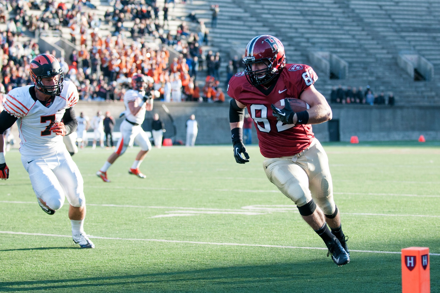 Tight end and long snapper Tyler Ott '14 heads for the end zone on Harvard's home turf against Princeton. Despite eventually falling to the Tigers 51-48 in this triple-overtime thriller on October 26, 2013—the Crimson's only loss of Ott's senior season—Ott finished the game with three touchdowns, tying the program record for single-game touchdown receptions.