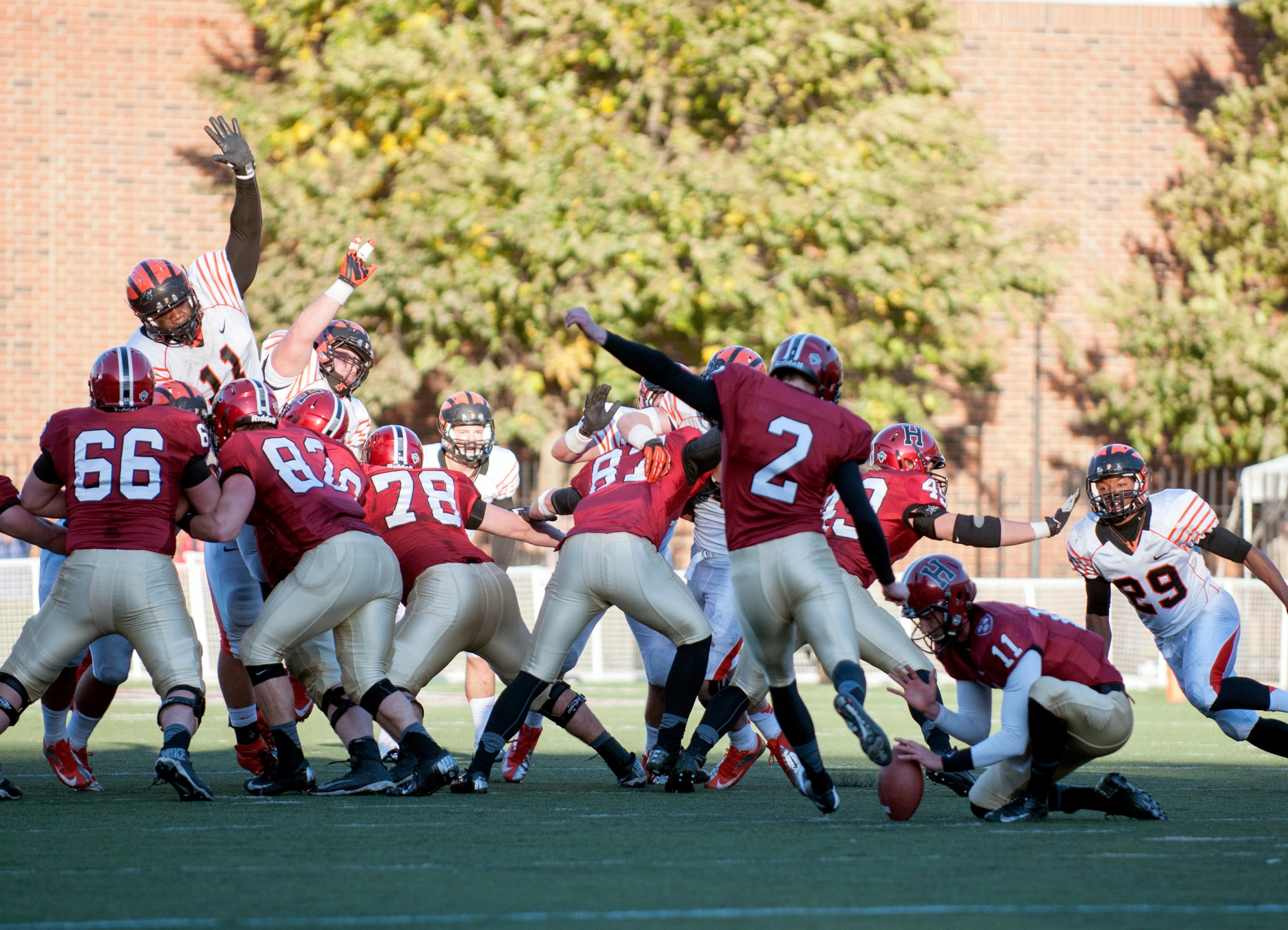 Tyler Ott '14, wearing number 82, blocks the Princeton defensive line with the rest of the Crimson kicking unit after delivering the snap to kicker Andrew Flesher '15 in a 2013 contest at Harvard Stadium.