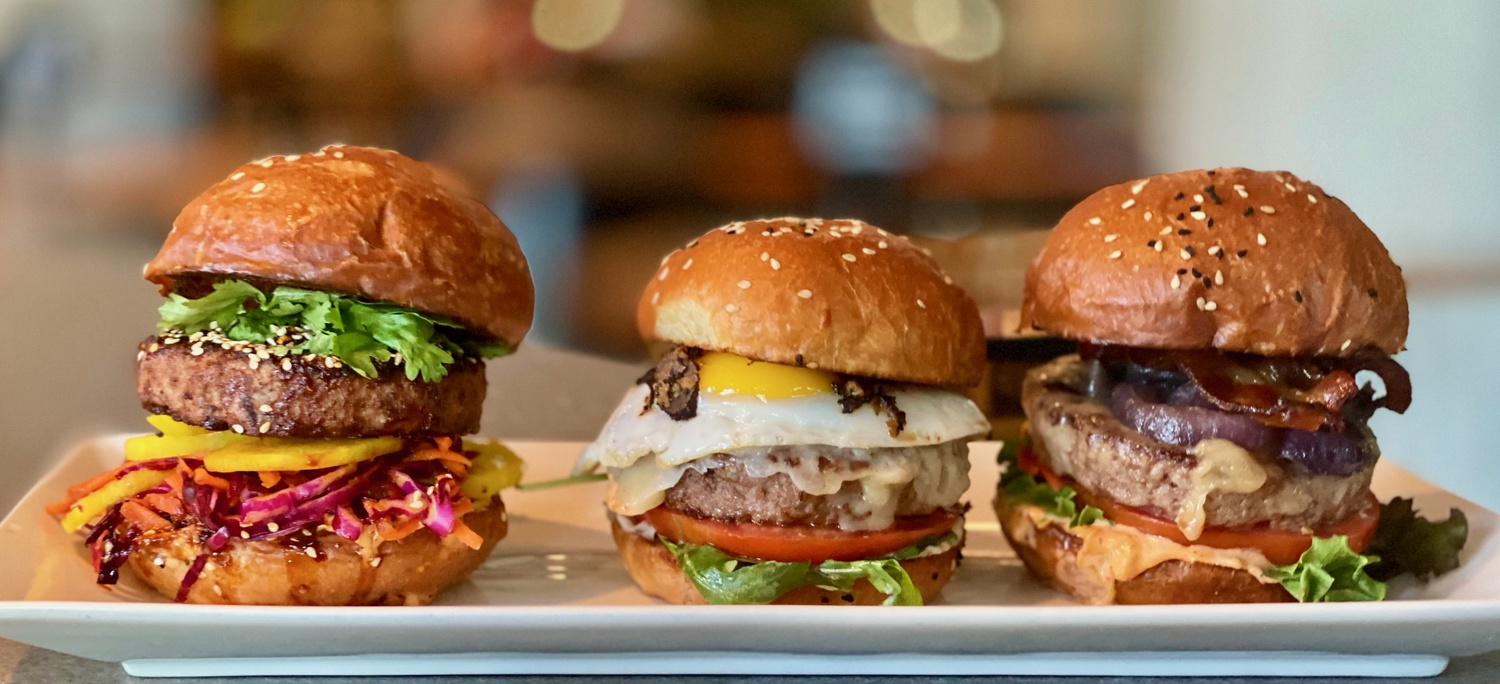 A trio of burgers on display at Nu Burger, a new burger venture that re-opened as a ghost restaurant after originally being in Time Out Market Boston.