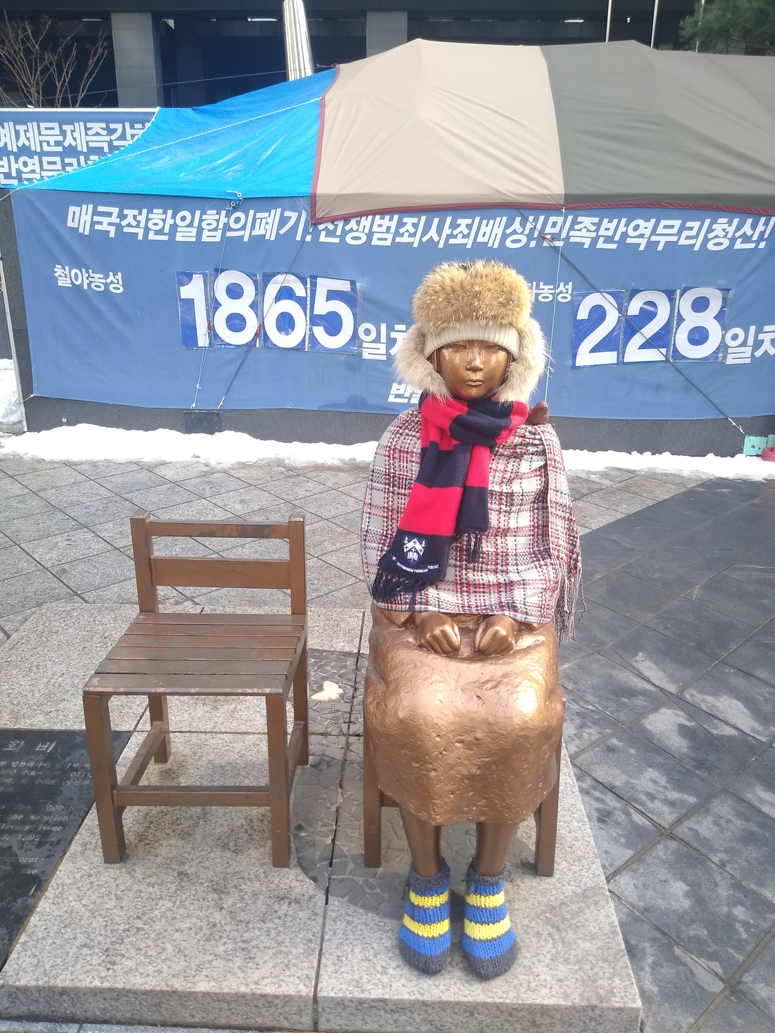 The Statue of Peace in front of the former Japanese Embassy in Seoul, South Korea commemorates comfort women, sex slaves taken by the Imperial Japanese Army during World War II. The slogans on the tarp behind the statue demand the Japanese government to make reparations.