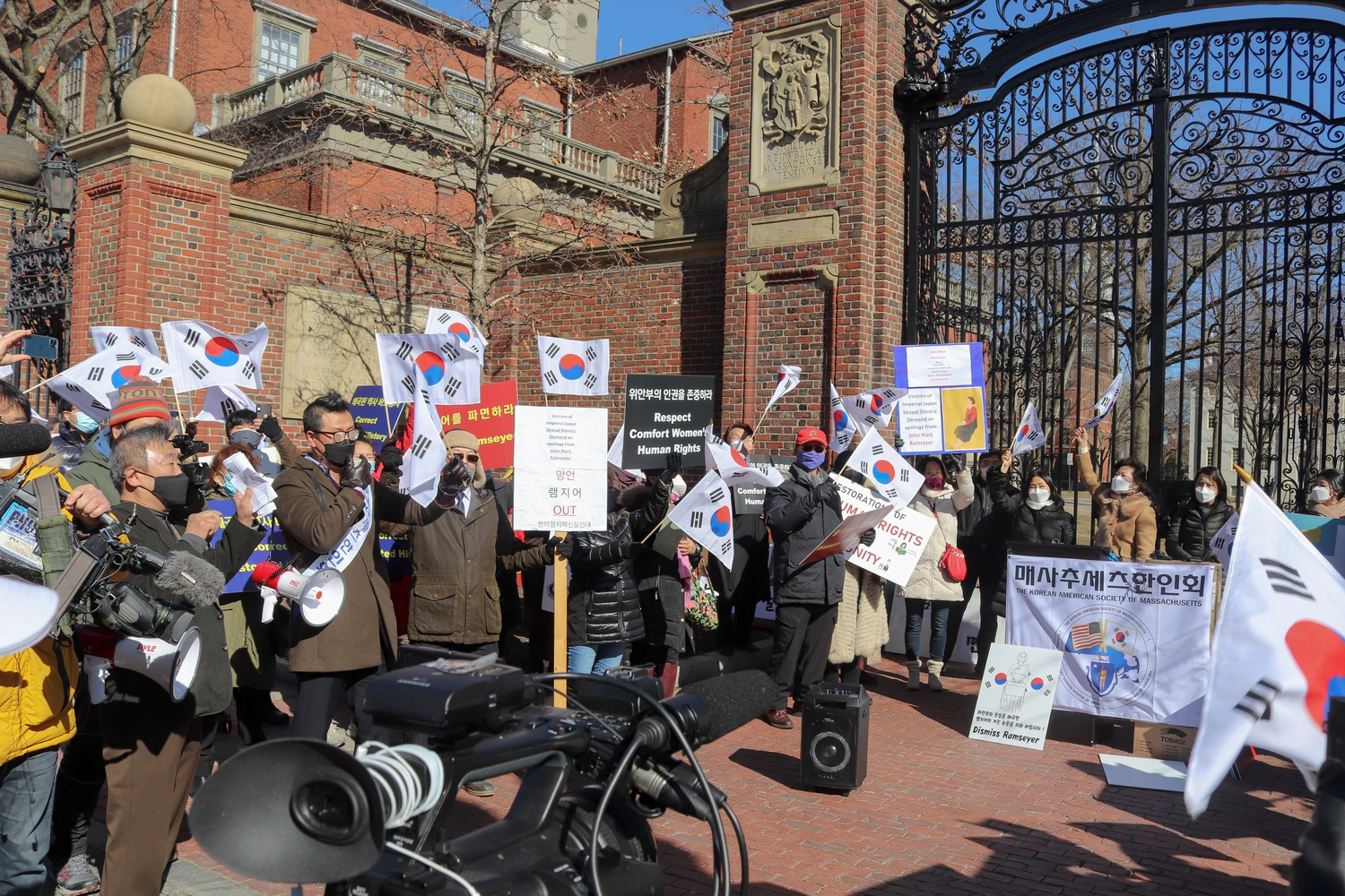 Dozens of demonstrators gathered outside Harvard Yard Saturday to protest Harvard Law professor J. Mark Ramseyer's upcoming paper on comfort women. Ramseyer has faced an outpouring of public criticism from government officials worldwide over the article.
