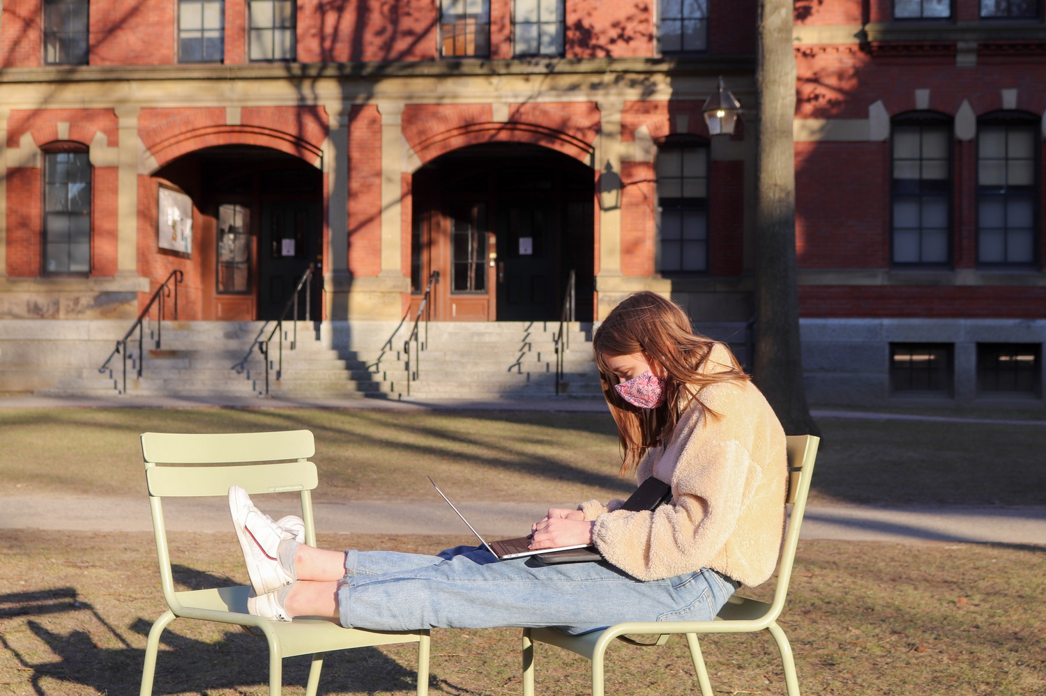 Layla Seaver '24 uses a laptop in Harvard Yard last month. On March 1, the University switched the campus status to Level 4: Lime, relaxing some of the public health restrictions faced by on-campus students.