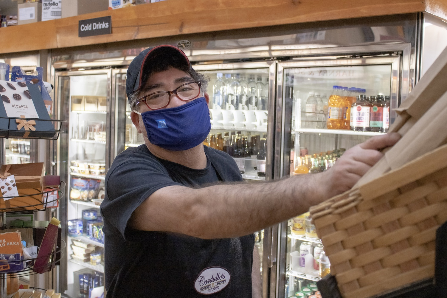 An employee at Cardullo's Gourmet Shoppe on Brattle Street prepares fresh bread by the deli counter. Cardullo's has remained open, despite the pandemic, to provide gourmet delicacies and gifts, as it has since 1950.