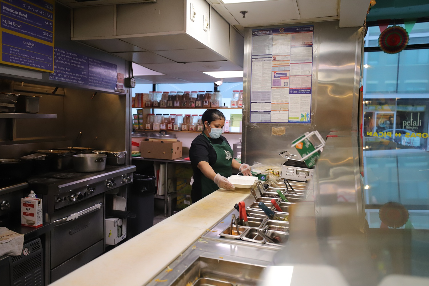 Gloria, a cook at El Jefe's Taqueria on Mt. Auburn Street prepares tacos for a takeout order. Unlike many other restaurants in Harvard Square, El Jefe's has not reduced its operating hours and remains open 20 hours a day, from 8 a.m. to 4 a.m.