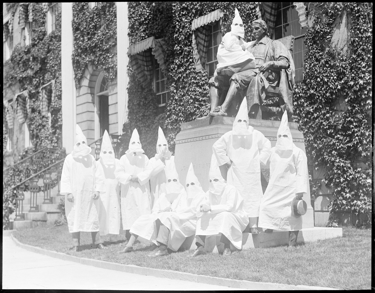 Harvard Klansmen pose for a second shot at commencement in 1924. One Klan member, sitting in the lap of the John Harvard Statue, with his body facing the statue turns his head towards the camera.