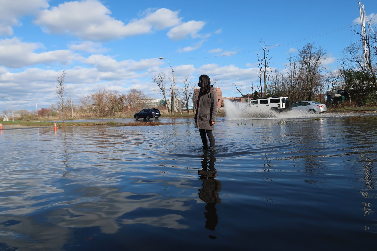 City Councilor Michelle Wu '07 surveys flooding at Morrissey Boulevard in Dorchester. As climate change causes sea level rise, these flooding events will become more common.