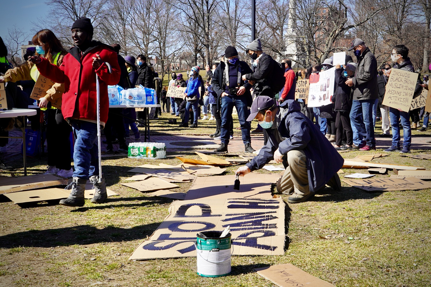 Attendees of the Rally against AAPI Violence in Boston Common paint signs with messages of solidarity.