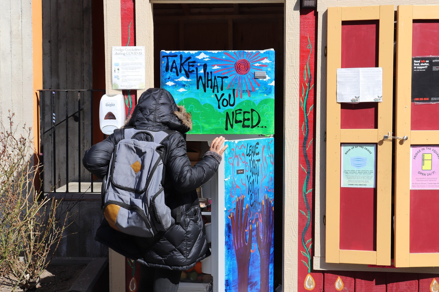 "Someone in Harvard Square peers into the ""Fridge in the Square."" This community fridge opened in January to help combat food insecurity."