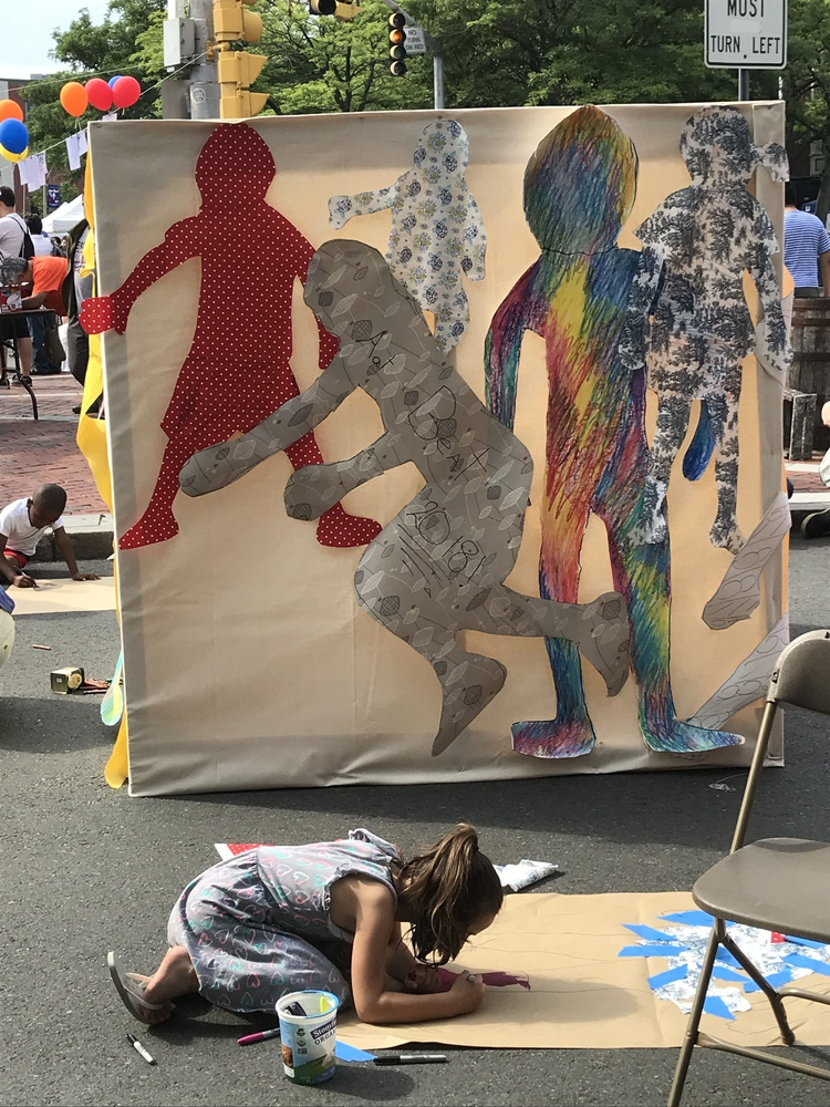 """In 2018, Christina M. Tedesco invited members of the Somerville community to make life-sized paper dolls of themselves, collecting them into a temporary mural called """"Traces of Bodies."""""""