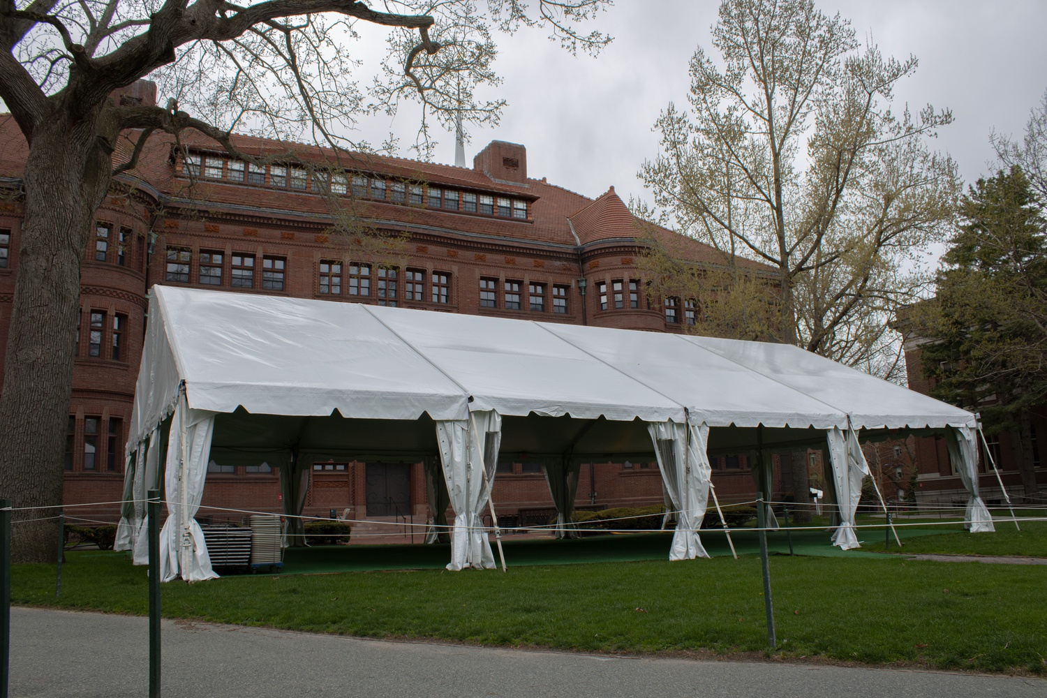 The College is experimenting with in-person and hybrid courses to develop best practices for in-person teaching and learning, with some classes being held in a tent behind Sever Hall.