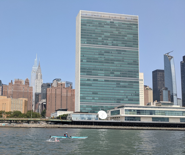 Joe Kaufman '89 powers past the Manhattan skyline, accompanied by a boat and kayak to provide cover.