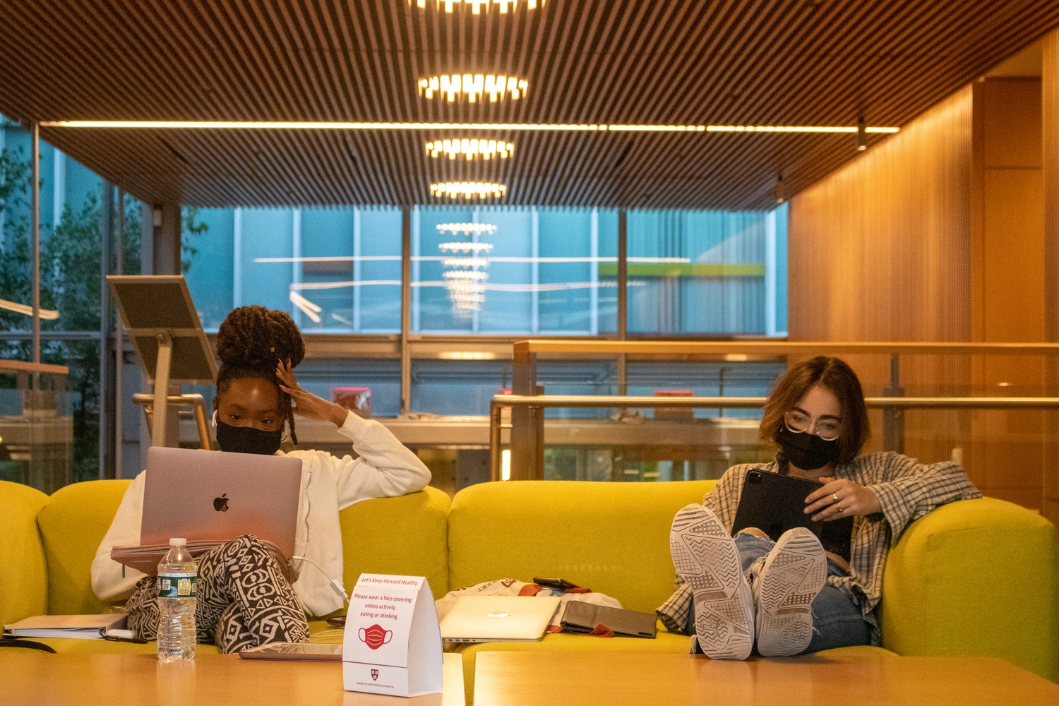 Masked students use laptops at the Smith Campus Center.