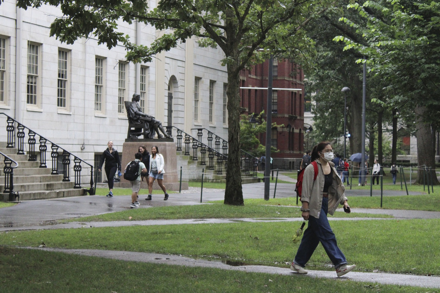 Students walk through Harvard Yard on the first day of classes Wednesday. For many students, the day marked the first time they received in-person instruction in more than a year.