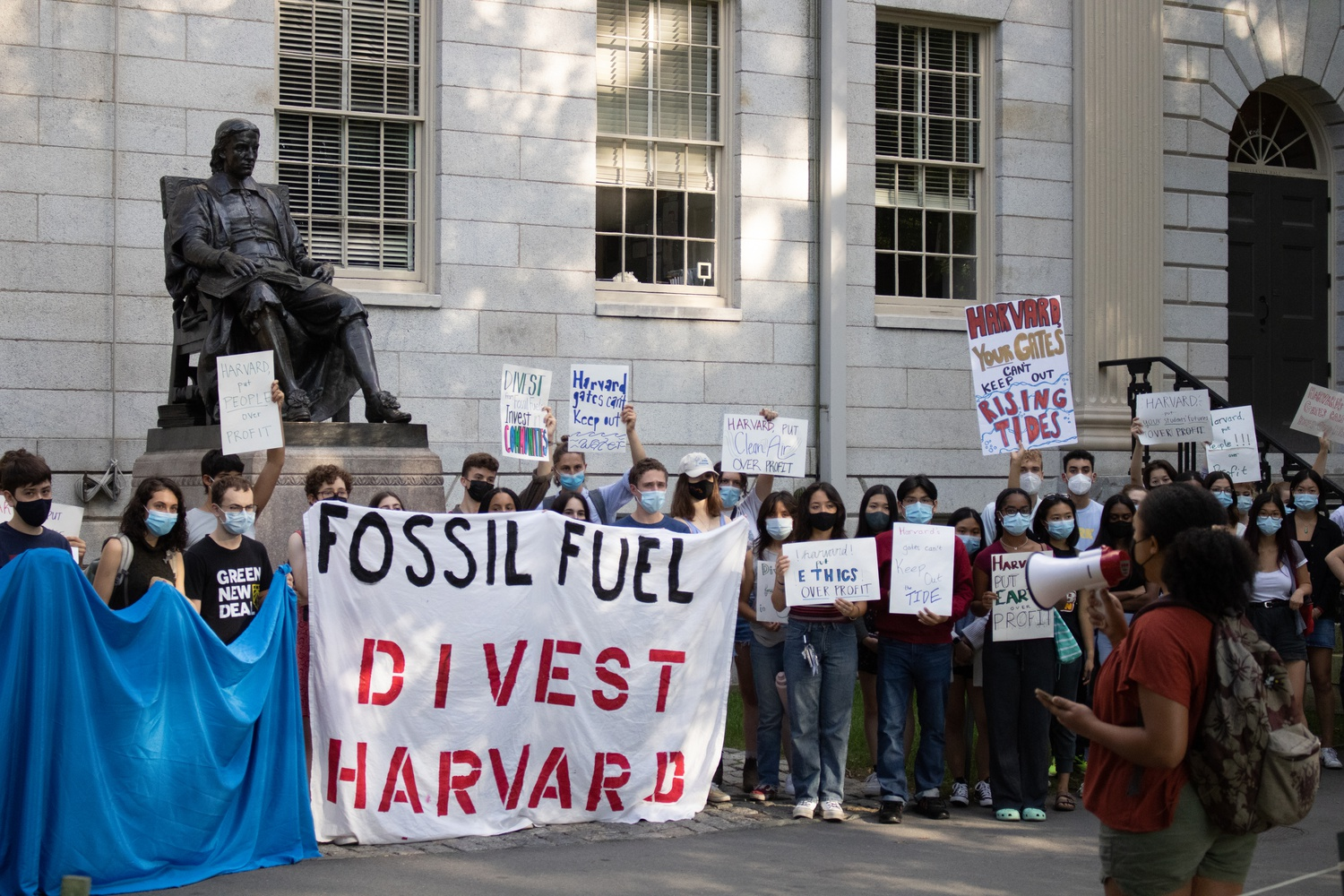Students held signs advocating for Harvard's divestment from fossil fuels in front of University Hall Tuesday afternoon.