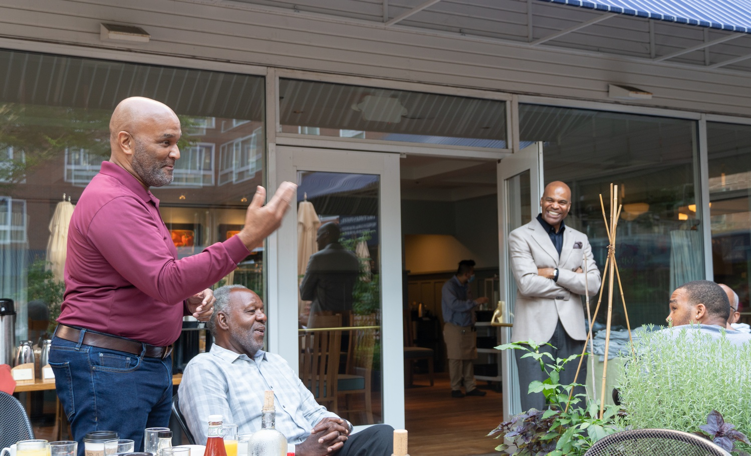 Victor A. Clay, the new chief of the Harvard University Police Department, left, speaks Wednesday morning at a breakfast organized by men's basketball coach Tommy Amaker at Henrietta's Table.