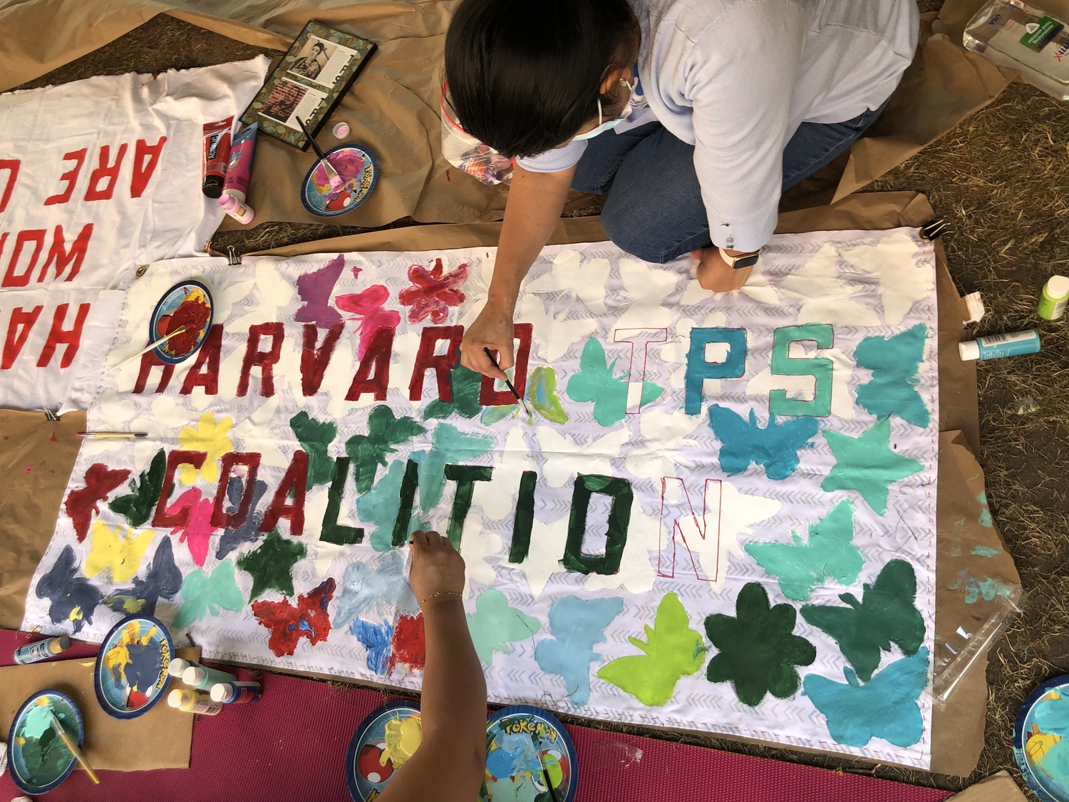 Doris Reina-Landaverde, a custodian and one of the co-founders of the Harvard TPS Coalition, paints a sign in preparation for the Sept. 20 National TPS Alliance march in Washington D.C.