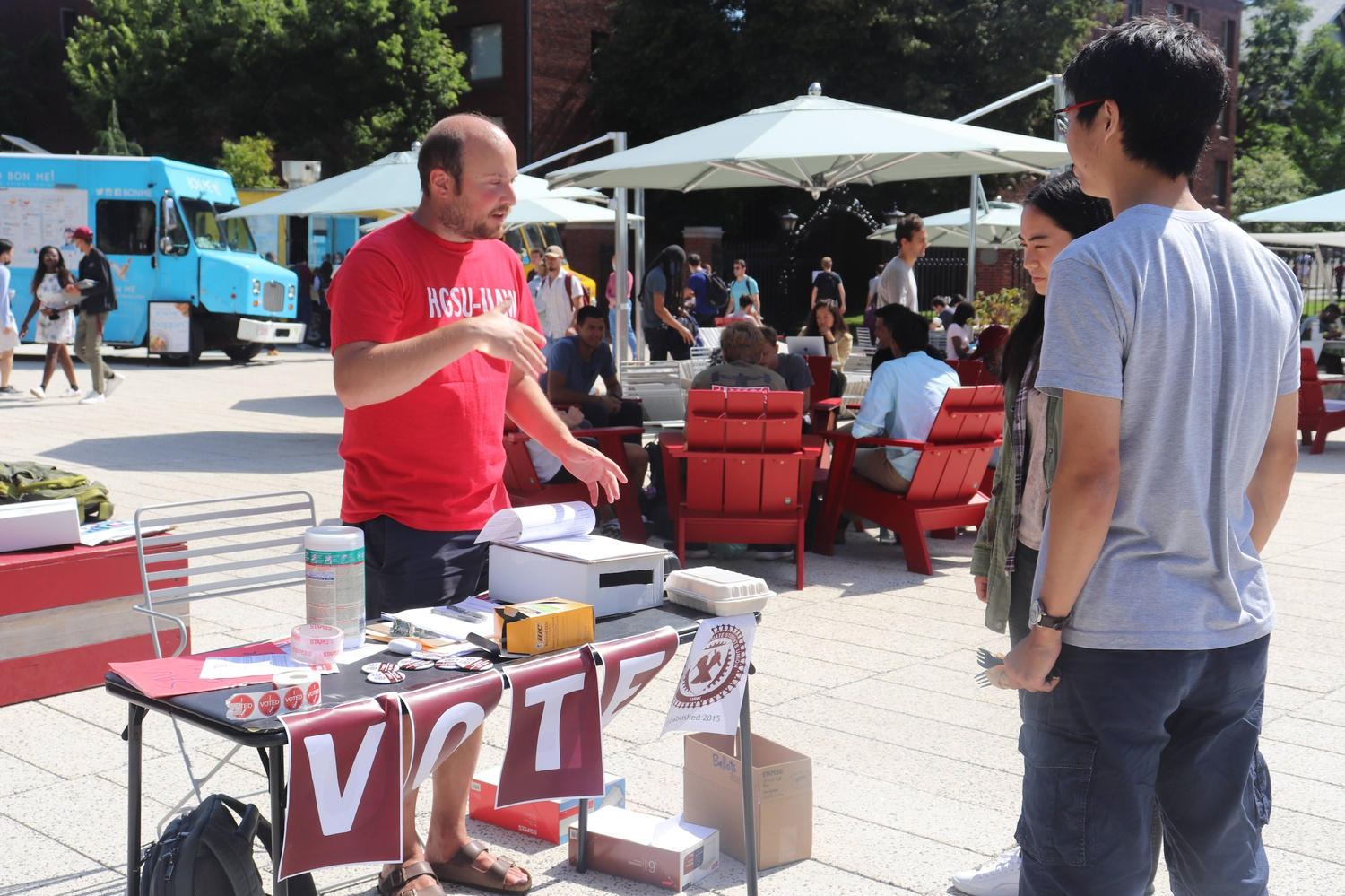 Andrew Bergman, a member of the Executive Board of the Harvard Graduate Students Union, converses with two students on the Science Center Plaza.