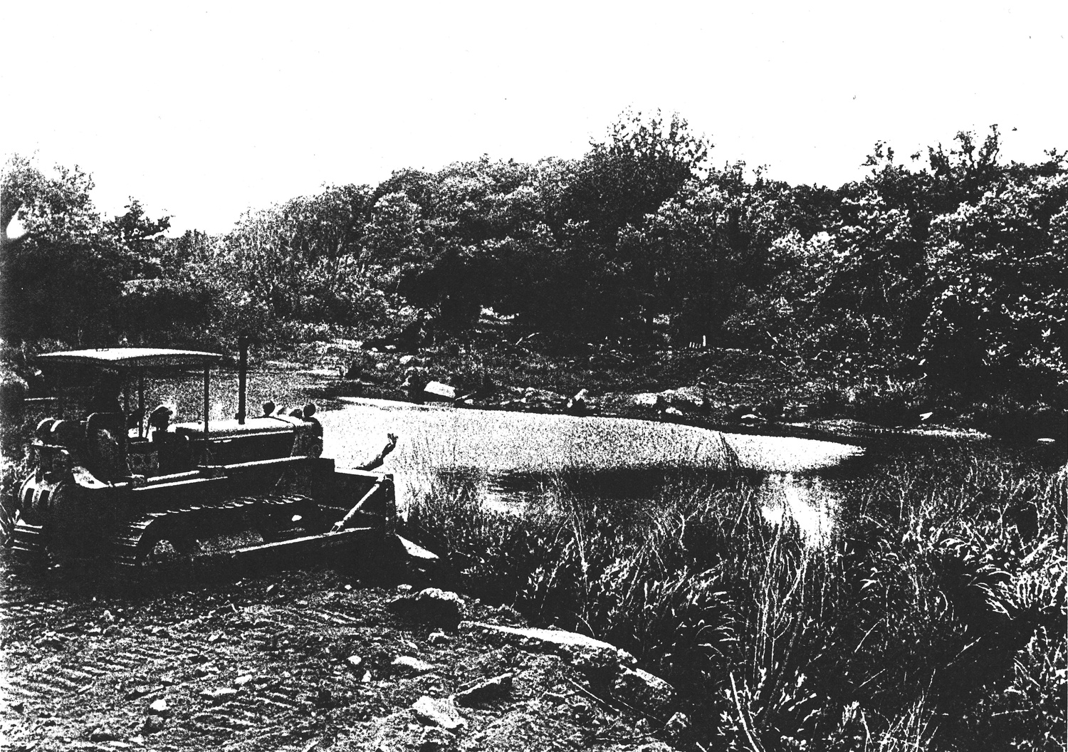 Following campus demonstrations, workers under the direction of Harvard and the City move granite blocks to partially fill in Muddy Pond in June, 1971 in this archival newspaper clipping.