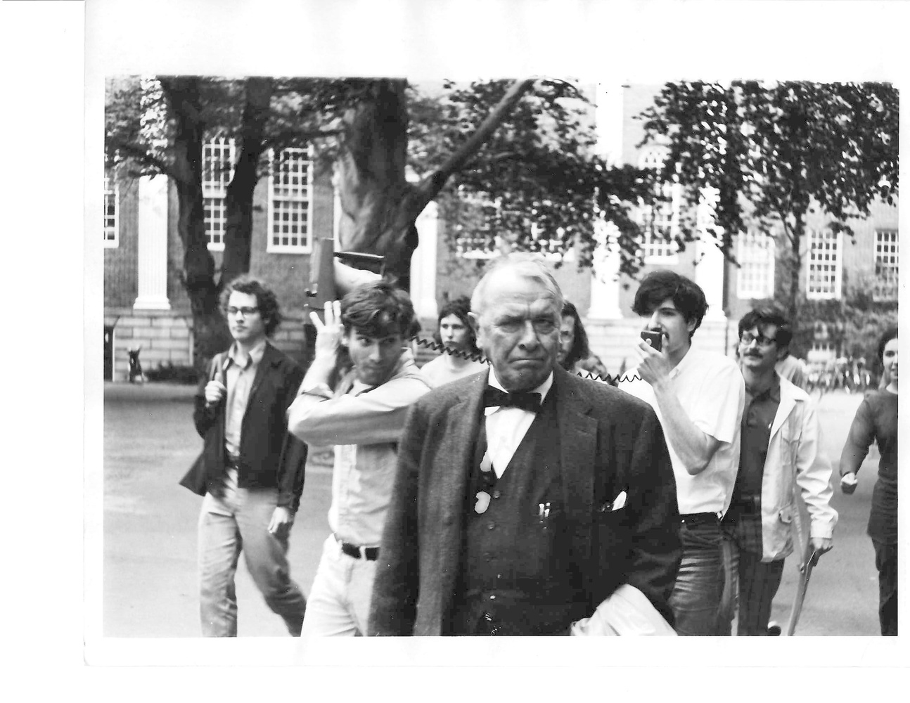 Students for a Democratic Society members tail and shout at Sargeant Kennedy '28, the Harvard Corporation secretary, through Harvard Yard. Ira D. Helfand '71 is pictured holding a bullhorn.