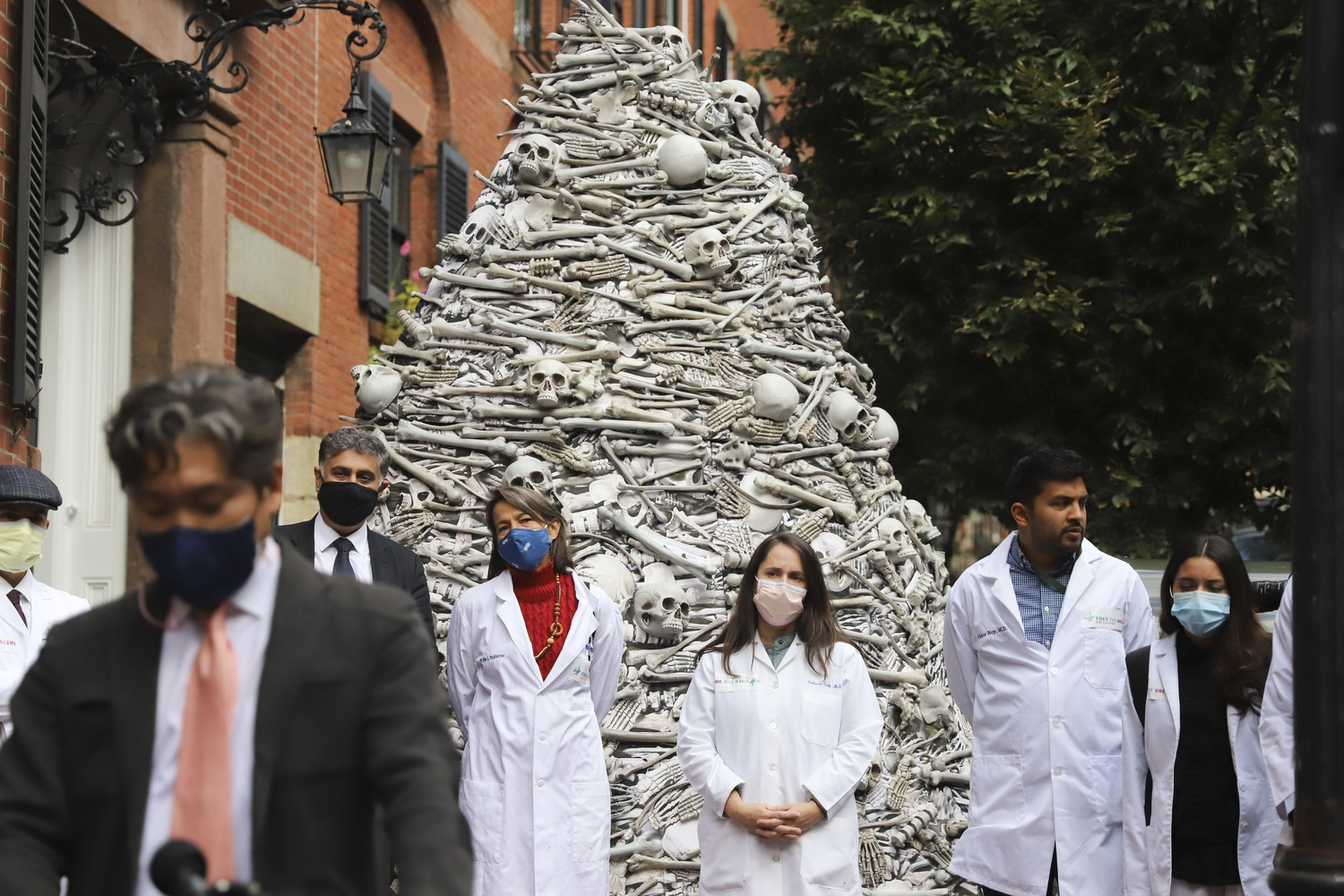 A group of Harvard-affiliated doctors called for global vaccine equity outside the home of Moderna's CEO Wednesday, speaking in front of a 12-foot high display of artificial bones.