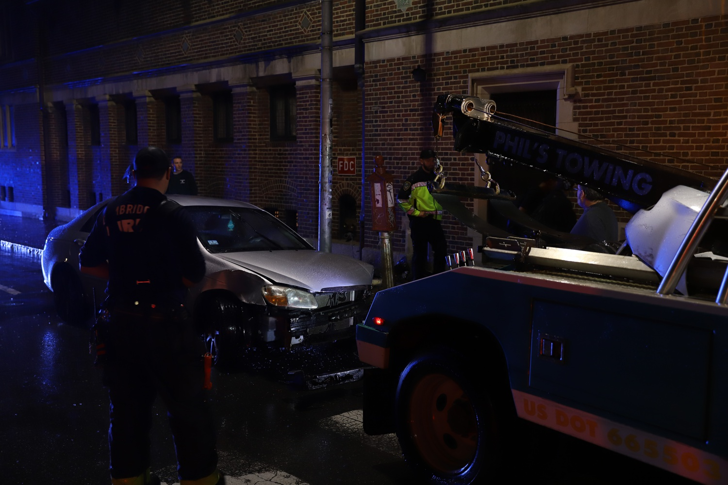 A tow truck removed the gray sedan after it crashed into the Harvard Lampoon building.