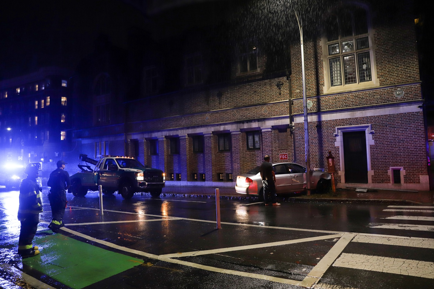 Emergency personnel at the scene after a car crashed into the Harvard Lampoon building Sunday night.