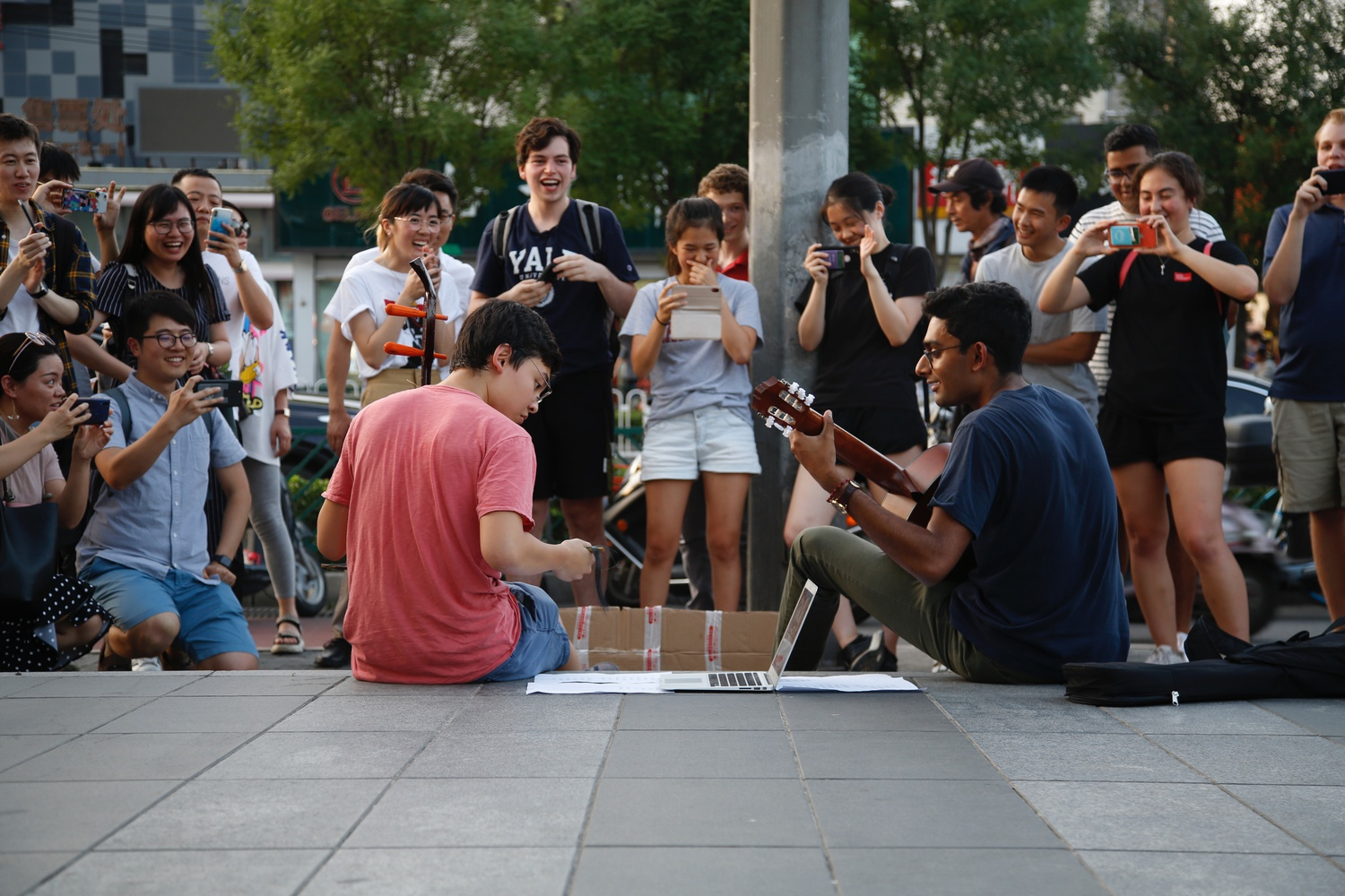 Two students performing Chong'ai on er'hu and guitar in Wudaokou square in Beijing, China.