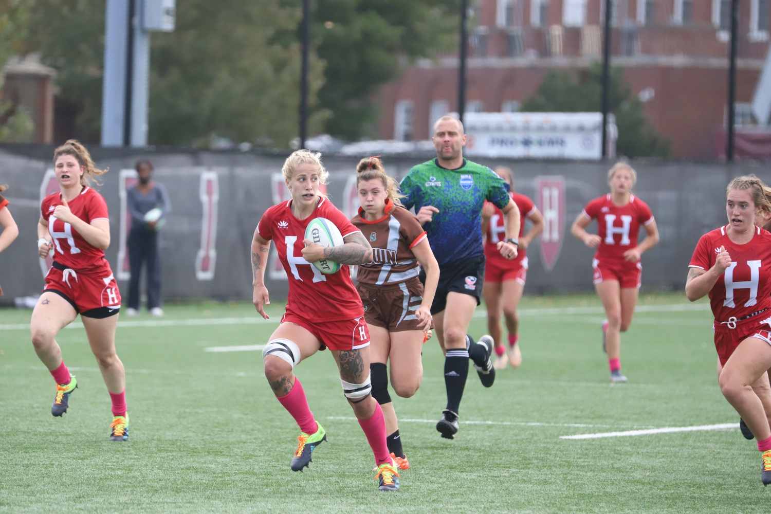 Senior prop/lock Erica Jarrell sprints away from defenders during Harvard's win over Brown. Jarrell's Crimson remains undefeated on the season.