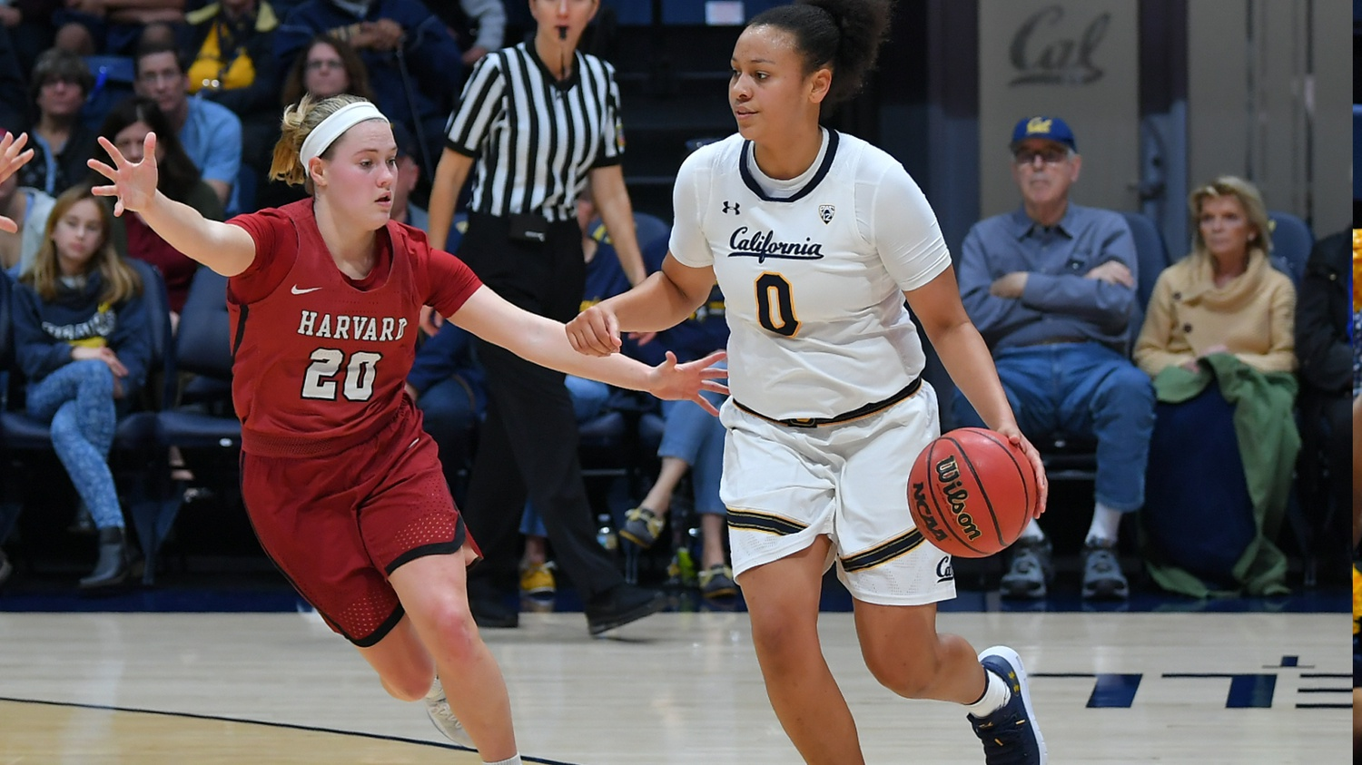 McKenzie Forbes, while playing for the Cal Golden Bears, dribbles at the top of the key as Havard's Madeline Raster defends.