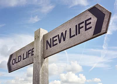 A sign post pointing to Old life in one direction and New Life in the other.