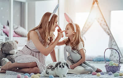 A mother and daughter wear festive bunny ears for Easter