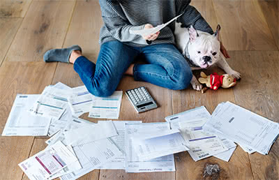 A woman sits with her dog, tax documents spread out across the floor.