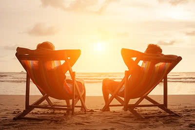 a couple relaxing in beach chairs, looking at the sunset