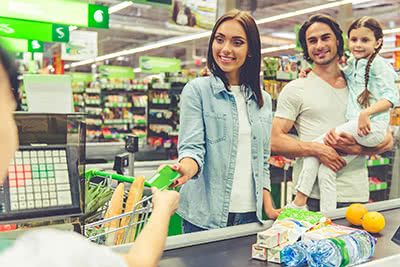 A mother hands the clerk her credit card while her smiling husband and daughter stand behind her in the checkout line.