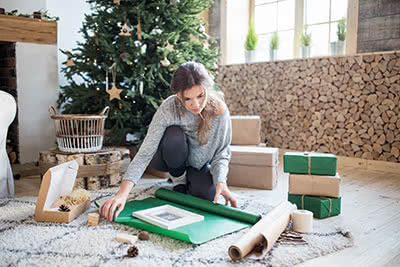 A woman begins wrapping a gift on the floor of her living room