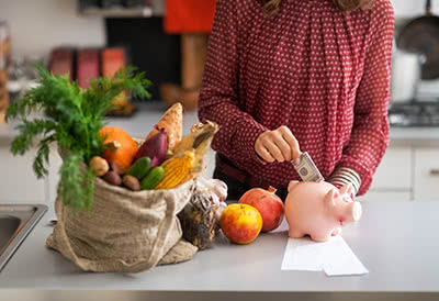 A woman puts extra money into a piggy bank next to a bag of groceries