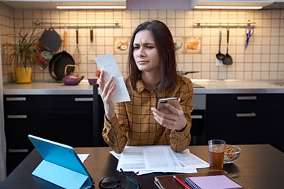 A woman makes a face while going over her tax documents.