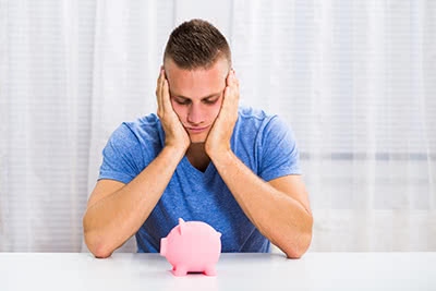 a young man holds his head in his hands over a piggy bank