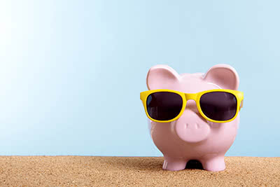 A piggy bank wearing yellow sunglasses