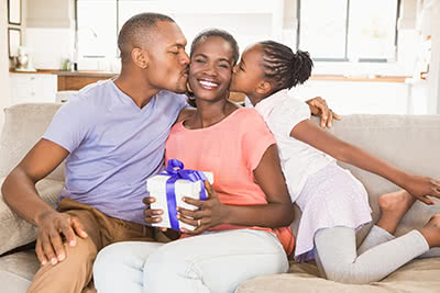 A family kisses their mother on the cheek while she holds a Mothers Day present.