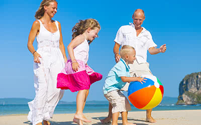 A happy family plays with a beach ball while on vacation