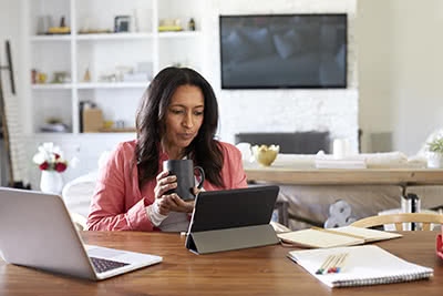 A woman holds a coffee cup while looking at her tablet on the kitchen table