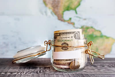 A small jar of money sits in front of a world map