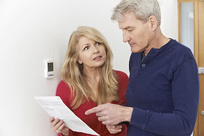 A man and woman look at a bill while standing at their thermostat.