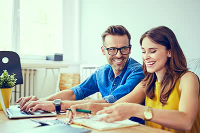 A smiling couple works out their finances at the kitchen table.